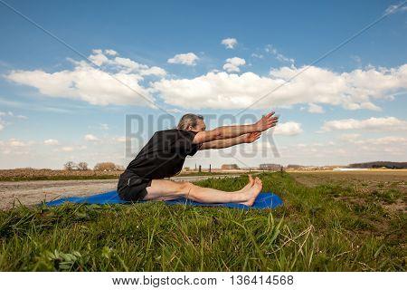 on an sunny day this man enjoys Paschimottanasana yoga in nature