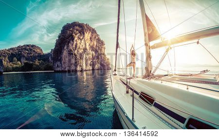 Young lady standing on the bow of yacht and doing exercise at sunrise