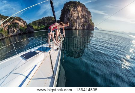 Two women standing on the bow of the anchored sailing boat and looking underwater