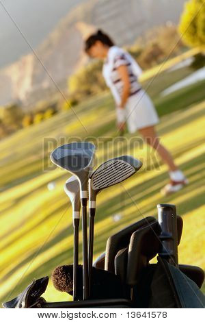 Bag of golf clubs outdoors and a player on the background