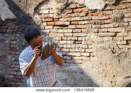 old Archaeologist using magnifying lens watching on ancient old in working site