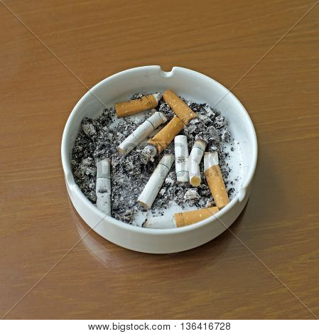 Smoked Cigarettes In White Ashtray