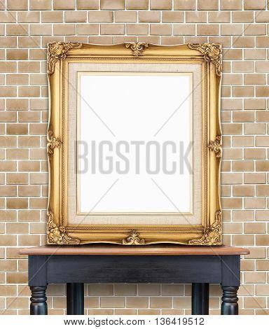 Blank Vintage Golden Photo Frame Lean At Pale Orange Brick Wall On Wood Table