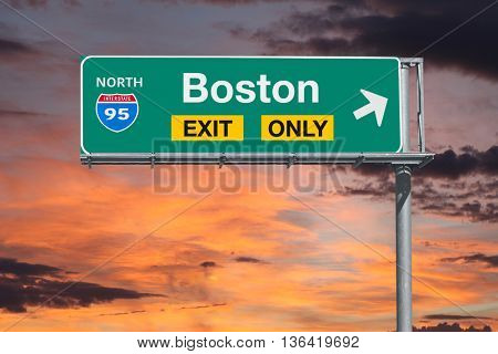 Boston exit only highway sign with sunrise sky.