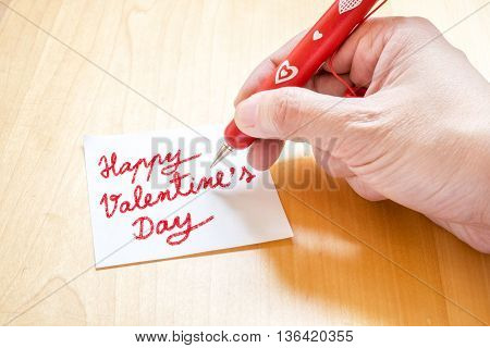 Hand Holding Red Pen With White Heart Pattern, Writing On Blank Notepad Paper On Wooden Table