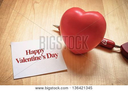 Happy Valentines day word on note paper with red heart and pen on wood table Love concept.