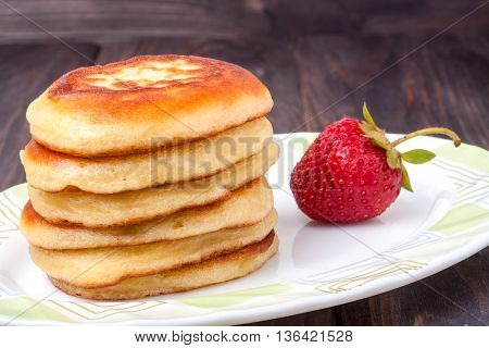 fritters on a plate with strawberries isolated on white background.