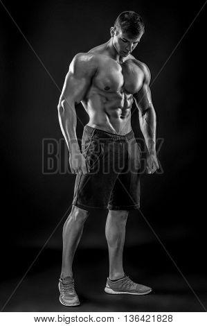 Muscular bodybuilder guy doing posing over black background. Naked torso in shorts. full height. Black and white, b w