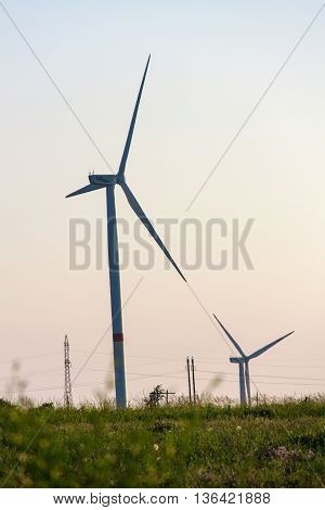 Wind turbines generating electricity on background of sky.
