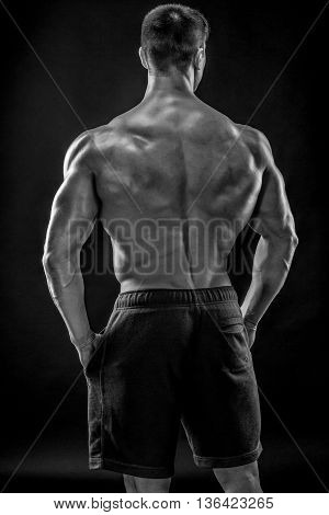 Muscular bodybuilder guy doing posing over black background. He turned his back Black and white, b w