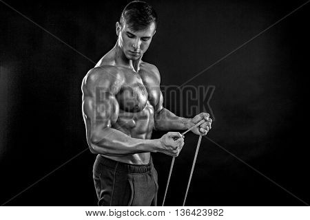 Young athletic man exercising and doing fitness with a chest expander, resistance band, on dark background. Black and white, b w