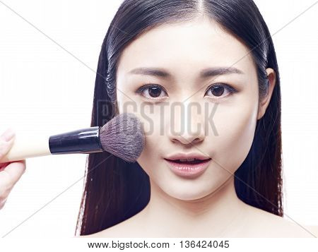 make-up foundation being brushed on to face of a young and beautiful asian model isolated on white background.
