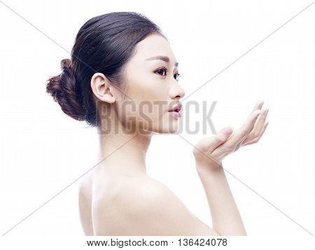 studio portrait of a young and beautiful asian model side view isolated on white background.