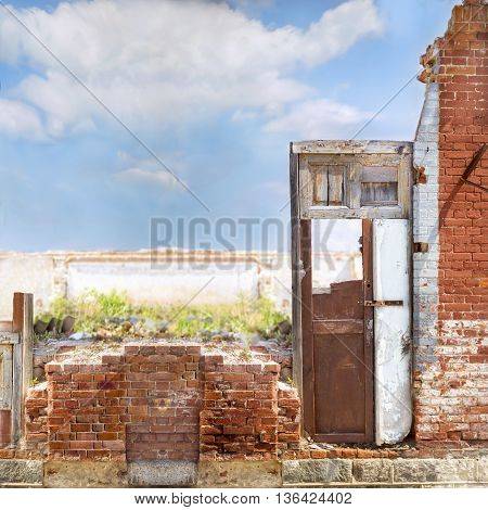 Old red brick house fragment with a wooden door in a blue cloudy sky background