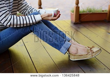 Woman Holding In Hands Cup Of Coffee With Milk On The Floor