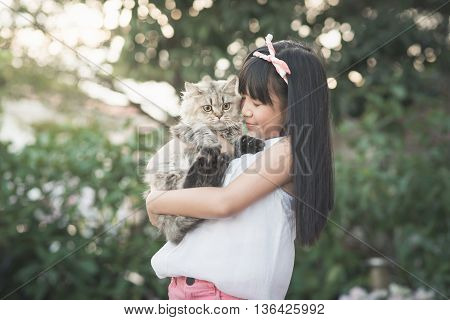 Beautiful Asian girl holding Lovely persian cat with sunshine in the park vintage filter