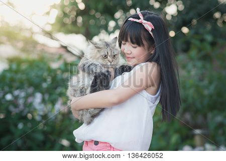 Beautiful Asian girl holding Lovely persian cat with sunshine in the park