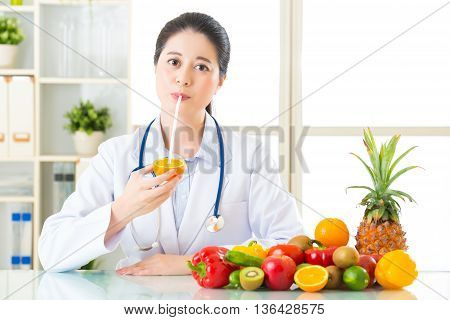 Young Asian Nutritionist Drinking Orange Juice