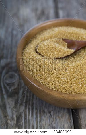 Cane sugar and spoon in a wooden bowl on the table