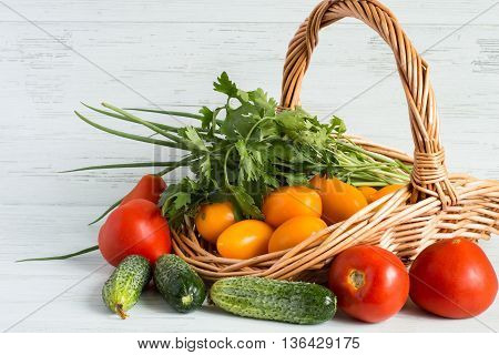 Fresh vegetables in a wicker basket on a light wooden background.