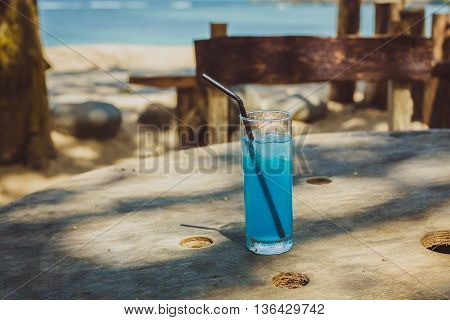 Blue alcoholic cocktail on a background of straw on the beach