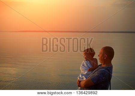 father and daughter admiring the sunset on the lake