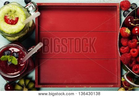 Healthy smoothies with fresh ingredients on wooden background