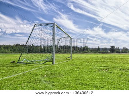 Soccer Goal on Soccer Pitch with a partly cloudy sky and trees.