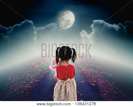 Back view of lonely child with doll sad gesture on pathway with a nightly sky and a large moon for halloween background. The moon were NOT furnished by NASA.