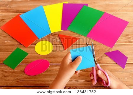 Child holds the scissors in his hands and cuts a square of color carton. A set of colored cardboard and a set of cut out geometric figures on a wooden table. Early childhood education