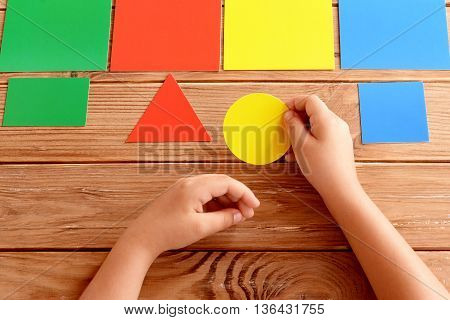 Child holds a yellow cardboard circle in his hands and puts on a corresponding color card. Child learns colors. Set of colored cards for kids of preschool age. Idea for learning in kindergarten, home