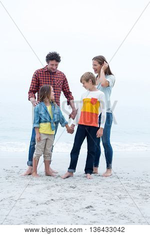 Full length of children standing with parents at sea shore against sky