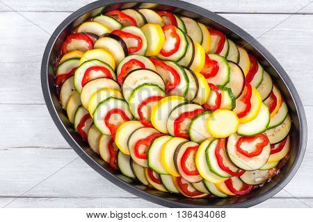 Raw ingredients for traditional French casserole ratatouille: slices of zucchini red bell pepper yellow squash eggplant in a baking dish view from above