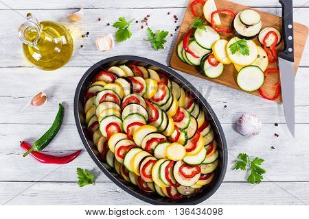 Layered ratatouille in a baking dish slices of zucchini red bell pepper chili yellow squash eggplant olive oil parsley and garlic on a white background close-up