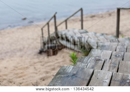Weathered wooden stairs leading to the beach from the sand dunes