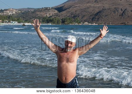 Man of mature age wide apart hands and enjoys the sea on the beach
