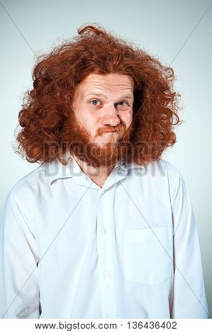 The young man with long red hair looking at camera with suspicion