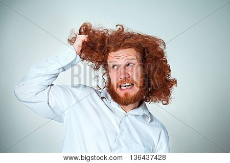 The angry young man with long red hair tearing his hair