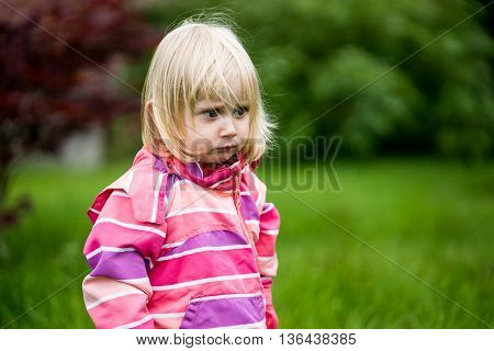 Sad or bewildered girl standing alone in the garden