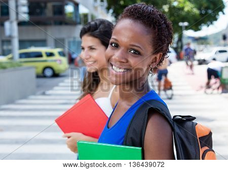 Happy african american female student with caucasian girlfriend in the city
