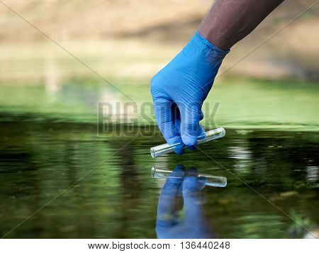 Water sample. Hand in glove collects water in a test tube. Concept - water purity analysis environment ecology. Water testing for infections permission to swim