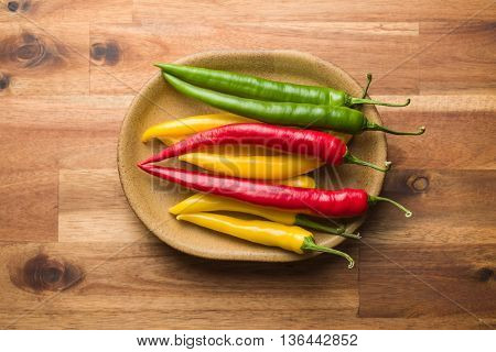 Different colors chilli peppers on wooden table.