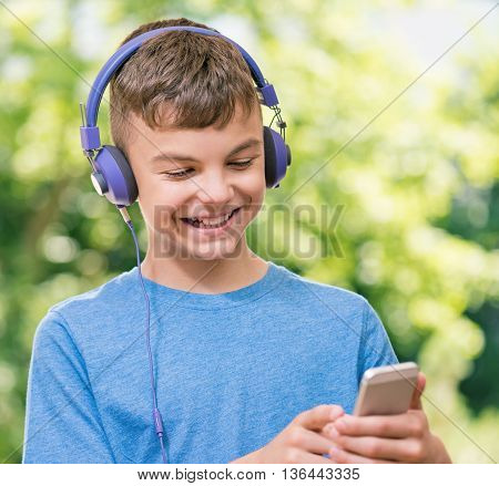 Outdoor portrait of happy teen boy 12-14 year old with cell phone - listening a music in headphones