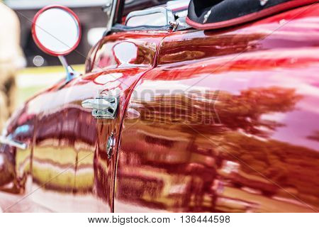 Close up photo of red veteran car with rear-view mirror and handle. Vintage car. Old automobile. Vibrant colors.