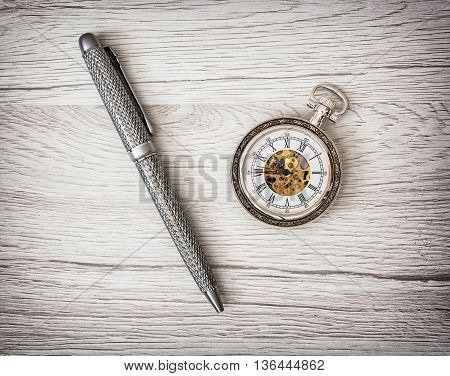 Retro pocket watch and exclusive pen on the wooden texture. Symbolic objects. Time management. Timing theme.