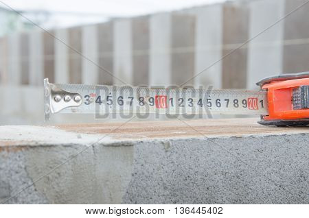 Construction Measuring Tape In The Hands Of The Worker, A Centimeter And A Meter, The Length Of The
