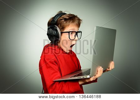 Cute boy in spectacles and headphones looking at his laptop monitor and shouting. Studio shot.