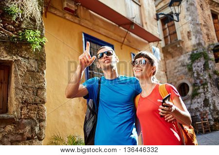 couple tourists walking in the old town. tourists considering the narrow streets of the city, happy and surprised