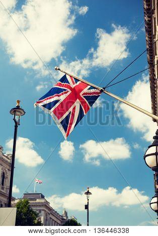 state sybols and national holidays concept - british nion jack flag waving on london city street