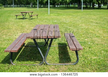 Wooden Picnic Table And Benches In Park